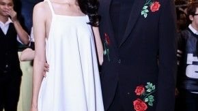 Nàng trông thực nữ tính trong chiếc đầm freesize phối chân ren trắng và chàng trông lịch lãm với vest đen điểm xuyến hoa hồng đỏ.
