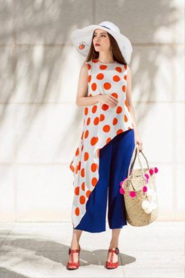 Yến Trang kết hợp áo vạt lêch họa tiết chấm bi cam cùng quần culottes màu xanh cô-ban. Sự tương phản của hai gam màu này vừa tạo nên sự nổi bật nhưng không làm người nhìn bị chói mắt nhờ sự lựa chọ họa tiết và phối hợp các mảng màu thông minh. Yến Trang lựa chọn túi cói, nón rộng vành làm phụ kiện đi cùng.
