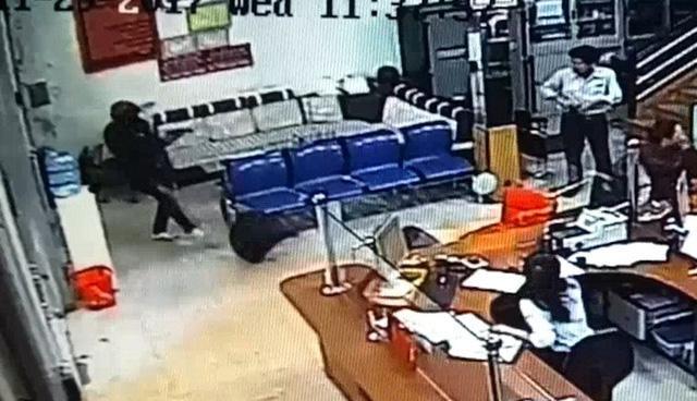 Thanh niên mặc đồ đen, kín mặt (trái) chĩa súng vào nhân viên bảo vệ, đồng thời đá túi vải về hướng nhân viên ngân hàng ý định cướp tiền – Ảnh cắt từ clip ngân hàng