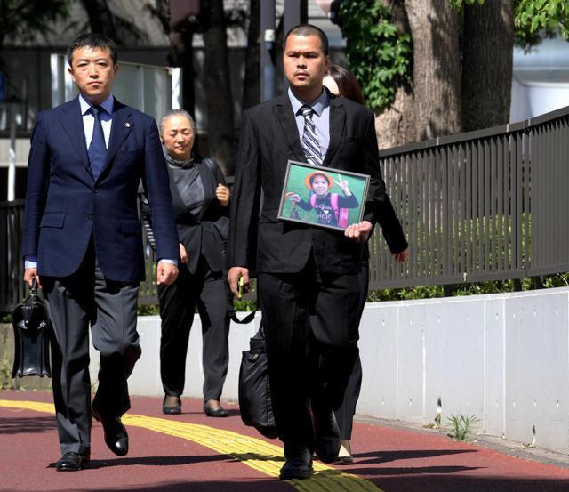 Anh Lê Anh Hào, bố của bé gái Lê Nhật Linh, cầm theo ảnh con gái xuất hiện trong phiên tòa.Ảnh: Asahi.