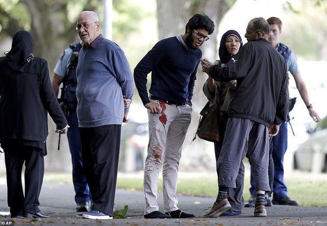 Một người đàn ông dính máu trên quần tại khu vực gần hiện trường vụ xả súng.