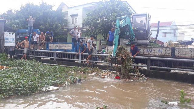 Xe cuốc đất móc rác đang tồn đọng tại cầu rạch Ông Trì (khu phố 3, thị trấn Dương Đông). Ảnh: VTC News