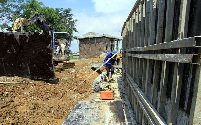 Lực lượng công nhân đang gấp rút hoàn thiện tuyến đê bê tông cốt thép để ngăn dòng nước lũ trong mùa mưa bão năm 2019.