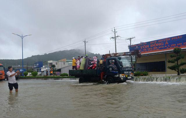 Xe tải đưa người dân cùng phương tiện qua đoạn đường ngập lụt. Ảnh: Dân Trí