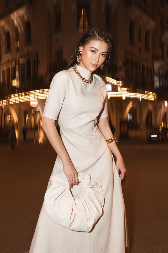 Phương Khánh lăng-xê xu hướng đơn sắc khi diện chiếc váy trắng cùng túi cầm tay xếp nhún. Cô cũng nhấn nhá set đồ với phụ kiện ánh kim vàng đồng lấp lánh.