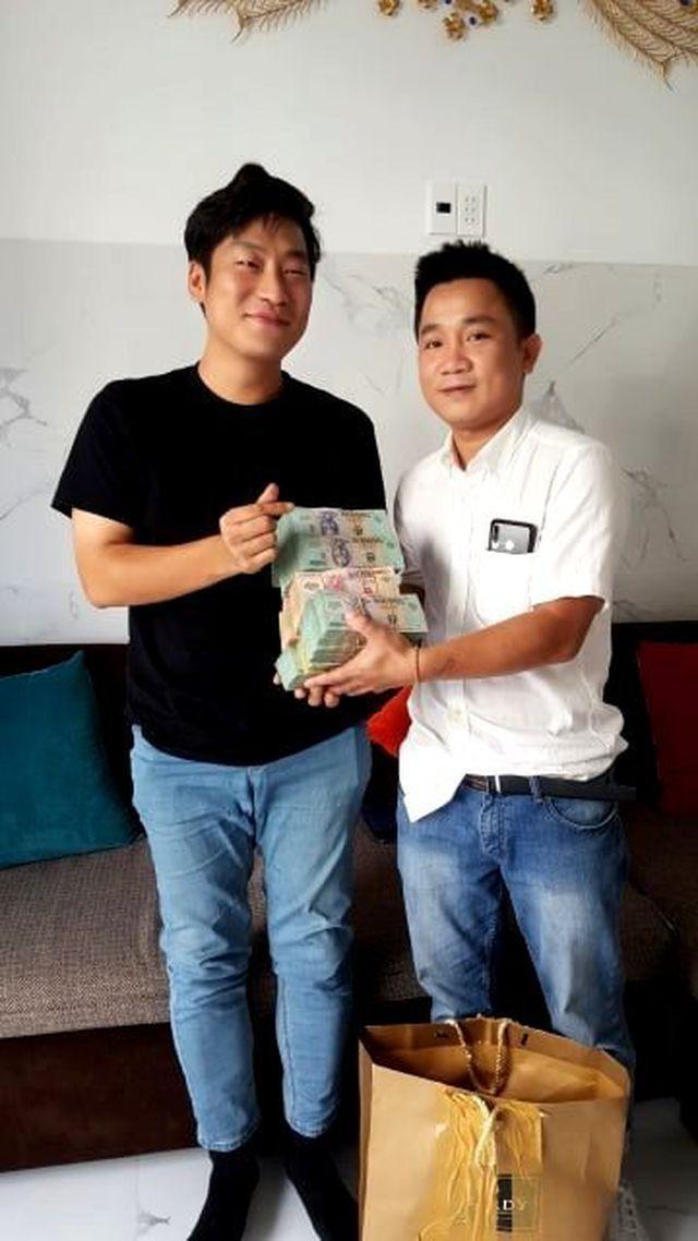 Anh Bùi Quốc Tuấn (phải) trả lại tiền cho du khách người Hàn Quốc