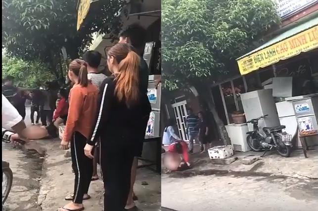 Cô nhân tình trần truồng bị người vợ (áo đỏ) lôi ra giữa đường đánh, chửi bới trước sự chứng kiến của nhiều người. Ảnh cắt từ clip.