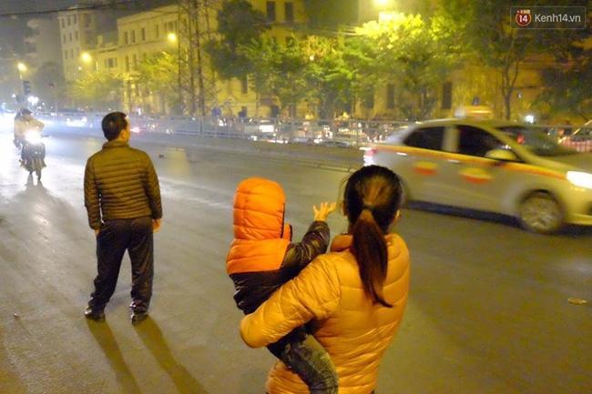 Một gia đình sốt ruột khi đứng chờ cả tiếng mà không bắt được chiếc xe nào.