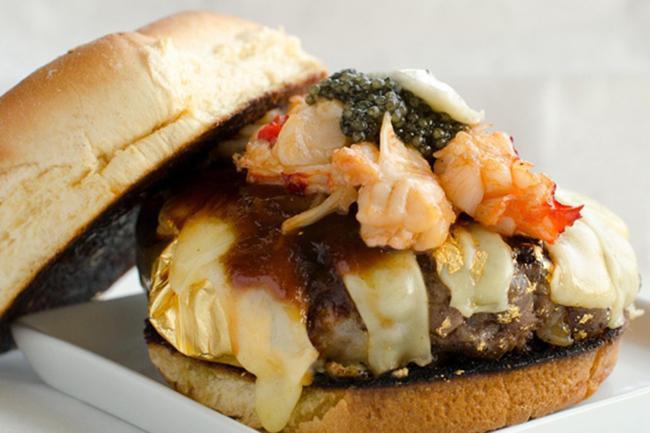 Nếu có 666 USD (khoảng 15 triệu VNĐ), đừng chần chừ gì nữa mà phải thưởng thức ngay món 666 Burger nổi tiếng của cửa hàng Douche Burger. Chiếc bánh này sẽ bao gồm miếng thịt bò Kobe đắt tiền, phô mai Gruyere nhập khẩu, trứng cá muối, gan ngỗng, tôm hùm và muối đặc biệt lấy từ núi Himalaya mang về. Đọc lướt về nhân bánh đã thấy đặc biệt nhưng để xứng đáng với mức giá 15 triệu thì tất nhiên vàng lá là điều không thể thiếu.