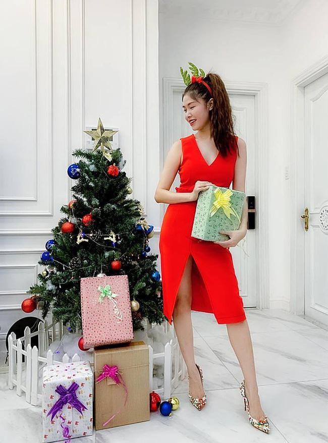 """Còn bà xã Đăng Khôi thì diện chiếc váy đỏ đúng màu chủ đề Giáng sinh đứng cạnh cây thông Noel khoe khéo dáng nuột nà của mình. Cô viết: """"Ông già Noel ơi, năm nay con đã rất ngoan lại còn chăm làm hơn 2 đứa nhóc nhà con, không biết con có may mắn được nhận quà không? Sao năm nào tụi nhỏ cũng có quà còn con lại không?""""."""