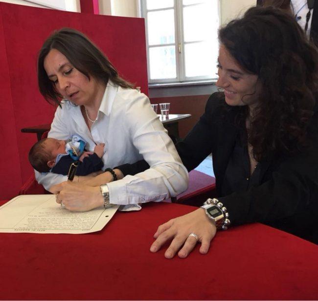 Cặp đôi đồng tính nữ đang điền tên của cả hai người để xác nhận là mẹ của đứa bé