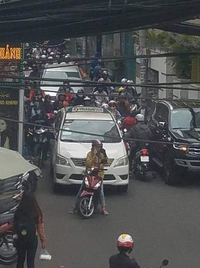 Người phụ nữ đi xe đỏ, mặc áo vàng ngang nhiên đứng nghe điện thoại giữa đường, bất chấp hàng loạt xe cộ phía sau không thể nhích được.