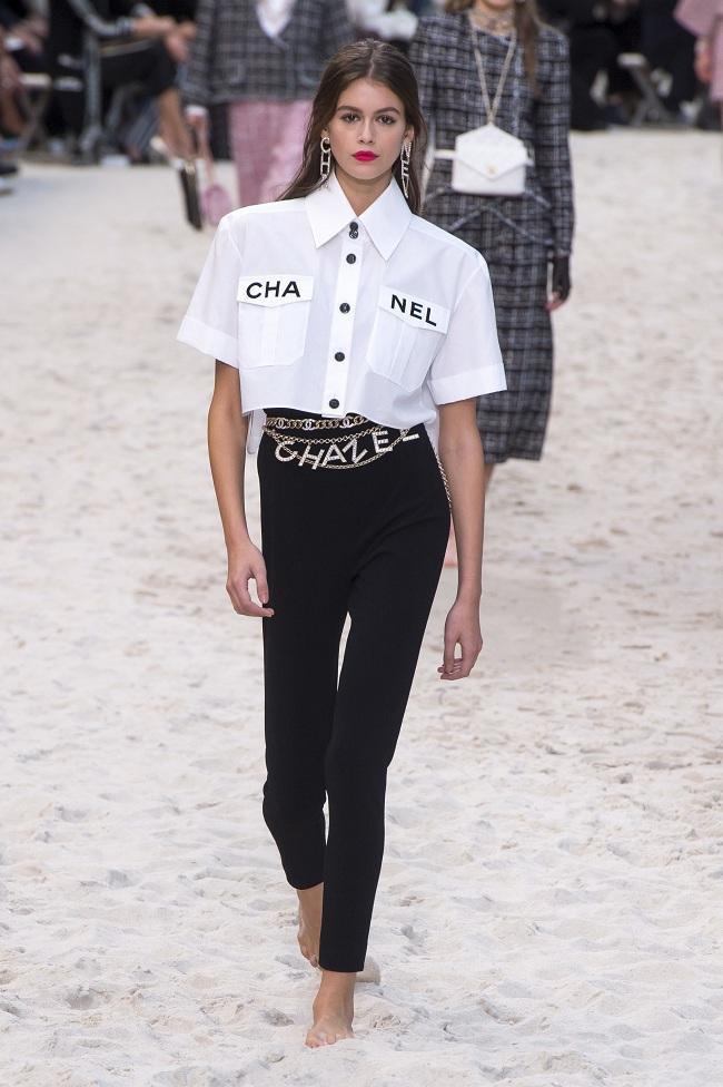 Set đồ áo sơ mi croptop mix cùng quần đen dài nhấn nhá chiếc thắt lưng xiềng xích lấp lánh thuộc BST Chanel Xuân – Hè 2019 được chân dài Kaia Gerber khoác trên mình sải bước trên sàn runway hồi năm 2018.