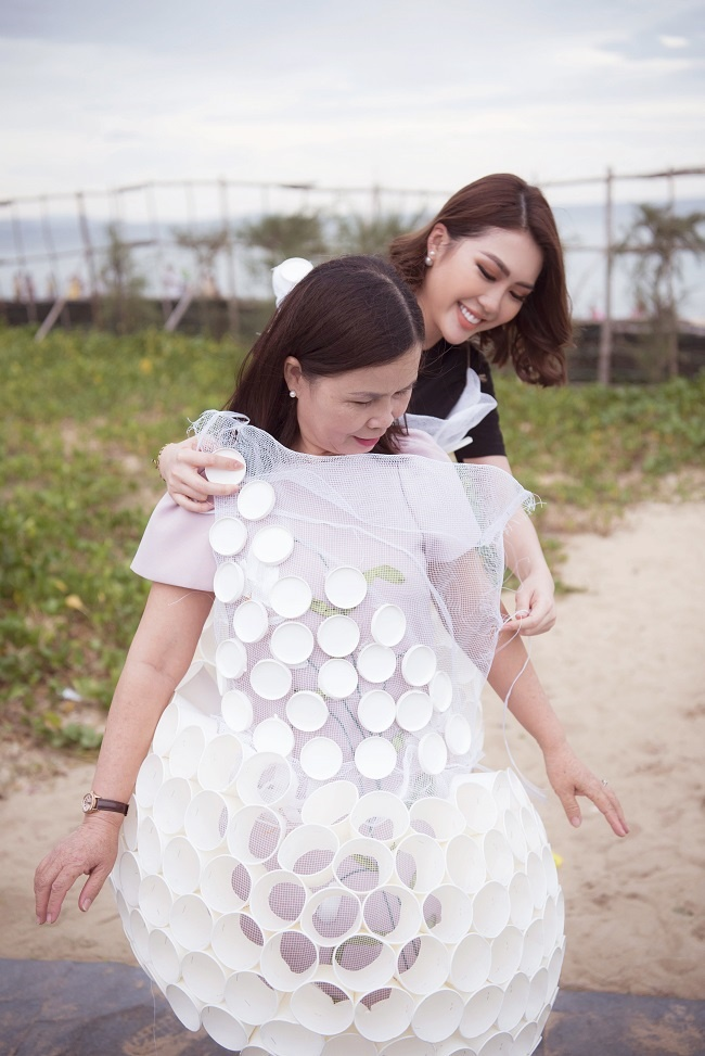 Người đẹp Phú Yên cẩn thận mặc cho mẹ mình chiếc váy làm từ các sản phẩm tái chế