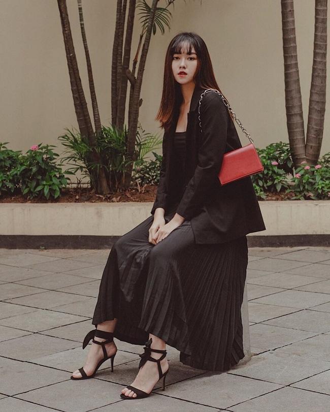 """Các style trang phục hàng ngày của Tường San đậm chất """" tiểu thư"""" kiêu sa, thanh lịch. Khoác trên mình một bộ váy đen dài xếp ly trông khá """"dừ"""" nhưng cô nàng vẫn biết nhấn nhá bằng các phụ kiện mix theo như túi xách đỏ nổi bật"""