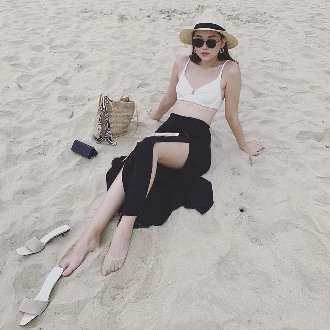 Kể cả trang phục đi biển, người đẹp cũng sẽ lựa chọn những thiết kế trắng, đen đơn giản để mix với nhau như áo bikini trắng mix cùng váy đen cắt xẻ chân cùng phụ kiện là túi xách và mũ vành chất liệu cói