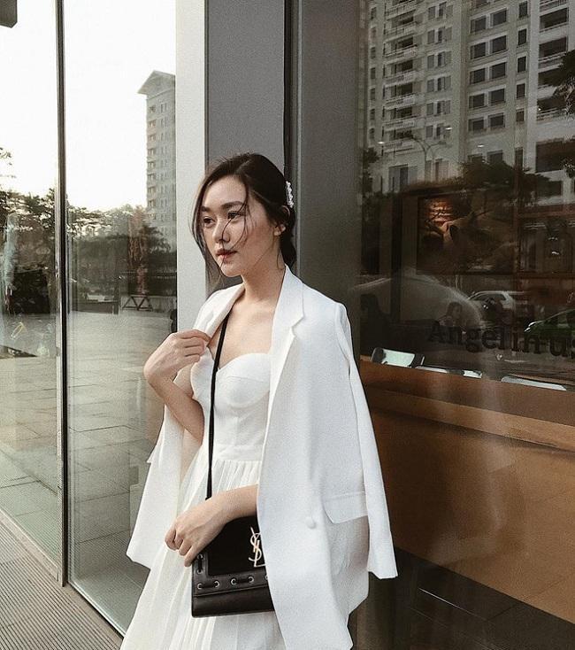 """Ngoài biết cách lên đồ với các trang phục hàng ngày, Tường San còn là một trong những tín đồ yêu thích """"đồ hiệu"""". Nhấn nhá với set đồ trắng này bằng chiếc túi YSL màu đen trị giá tầm 2.000 đô la Mỹ (hơn 45 triệu đồng)"""