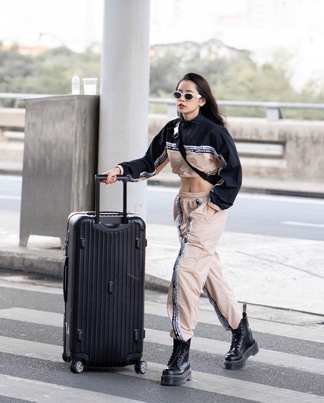 """Crotop tay dài """"matching"""" với quần jogger thể thao tông màu be mix màu đen của Chi Pu tại sân bay thu hút khán giả hâm mộ. Để tăng thêm độ cá tính, nàng ca sĩ diện thêm kính râm, fanny pack đen cùng đôi combat boot đế đen cực ngầu"""