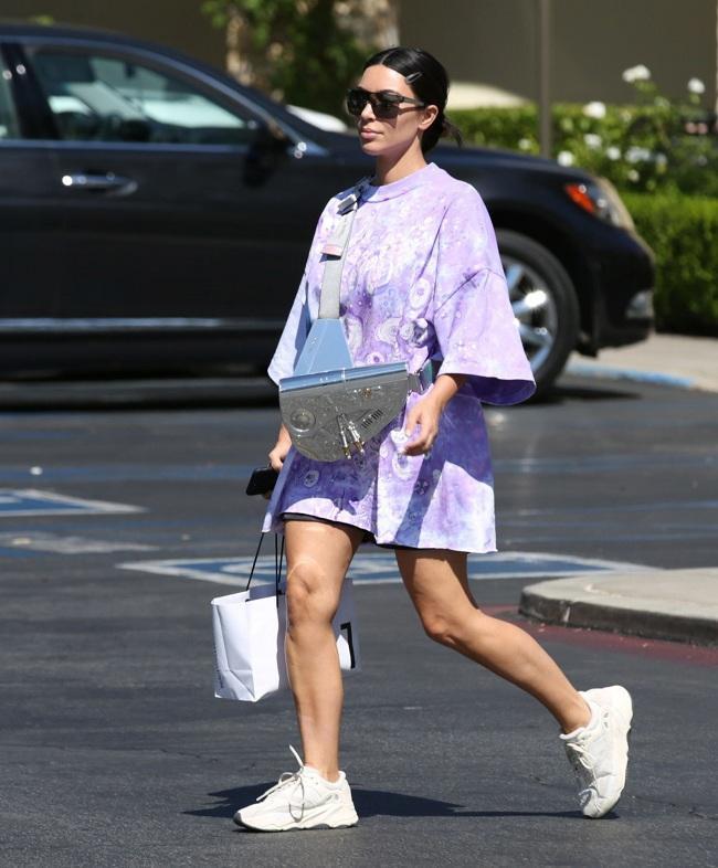 Kim Kardashian dạo phố với style trẻ trung gồm áo thun oversized màu tím mix cùng giày thể thao trắng cùng chiếc túi xách Dior màu bạc kim loại nổi bật
