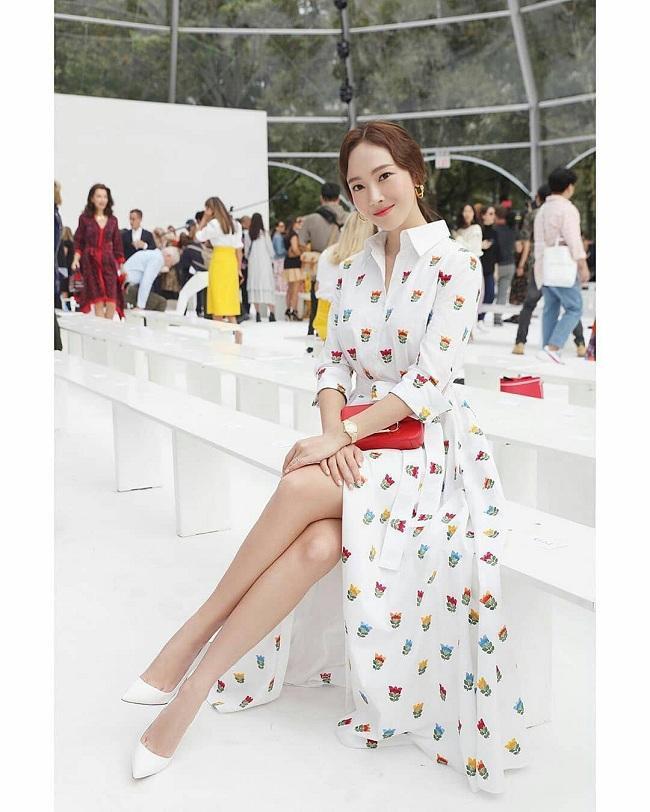 Jessica Jung chọn mẫu váy sơ mi trắng tô điểm họa tiết rực rỡ mix với giày cao gót bít mũi cùng clutch đỏ sang chảnh khi tham dự show diễn nhà mốt Carolina Herrera