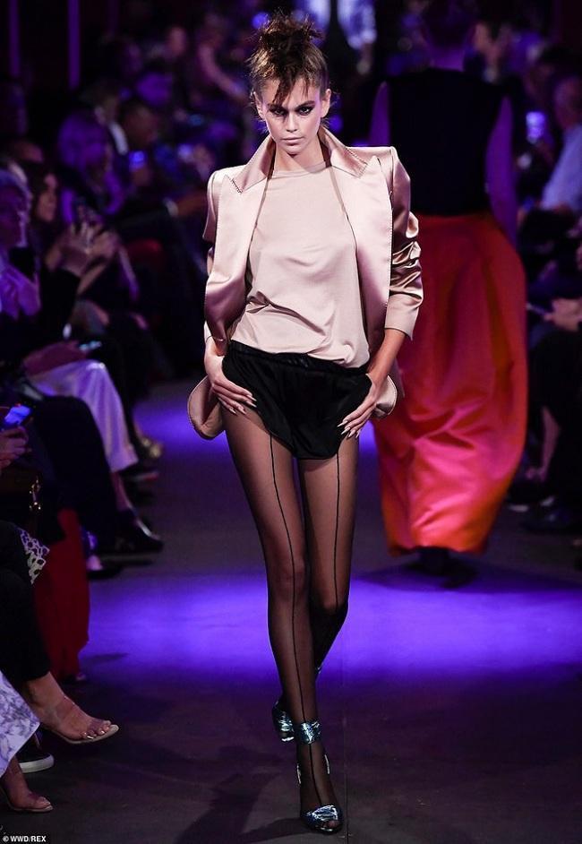 Chân dài Kaia Gerber đậm chất style punk/rock trong cách makeup và làm tóc. Trang phục độc đáo với chiếc áo blazer màu hồng nhạt xuyệt tông cùng áo bên trong mix cùng quần short đen trơn, kết hợp vớ lưới đen và giày cao gót bằng vải satin màu xanh đen.