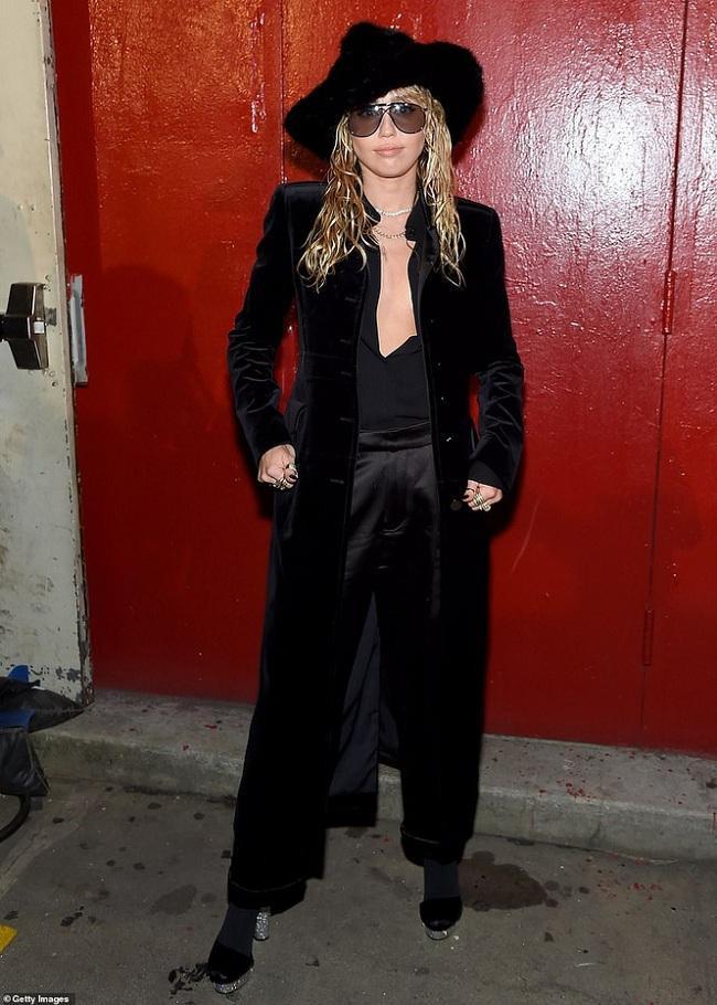 Miley Cyrus là khách mời VIP của thương hiệu. Cô chọn trang phục Jumpsuit đen không nội y mix cùng kiểu áo choàng nhung bên ngoài cùng phụ kiện mũ vành độc đáo