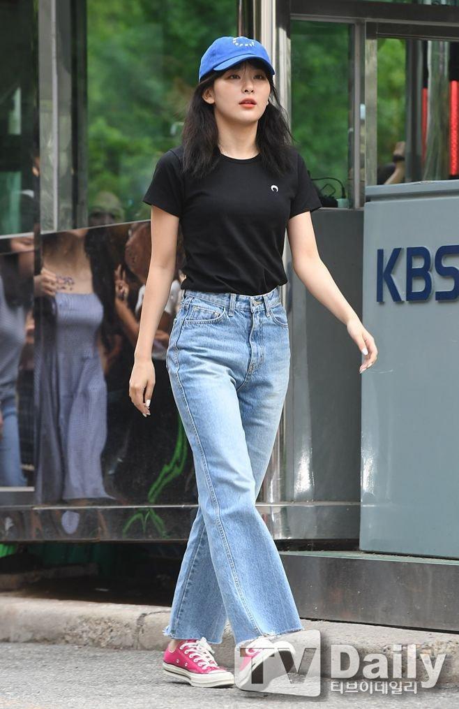 Cũng combo áo thun và quần dài nhưng Seulgi thì lại mang đến cảm giác năng động và trẻ trung khi chọn cho mình chiếc áo thun đen trơn đơn giản cùng chiếc quần jeans ống rộng đi kèm là đôi giày thể thao màu hồng nổi bật và chiếc nón kết màu xanh dương.