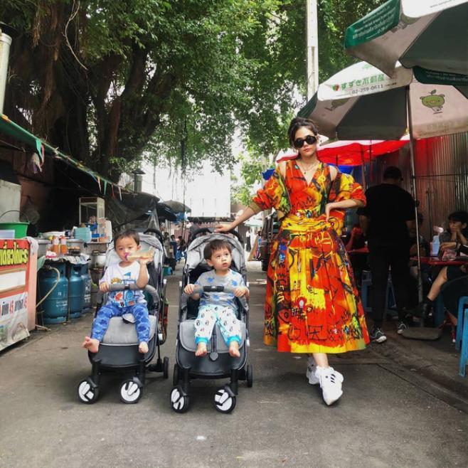 Trong khung cảnh đường phố giản dị, đơn sơ, Chompoo diện một chiếc váy rực rỡ và nổi bật, cô tạo dáng cực kỳ chuyên nghiệp bên hai cậu quý tử đáng yêuvới thần thái không hề kém cạnh