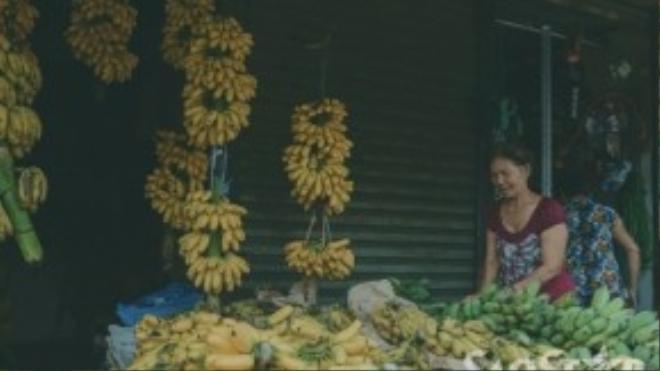 Những buồng chuối vàng ươm được bày biện mộc mạc tại một gian hàng ở đầu chợ.