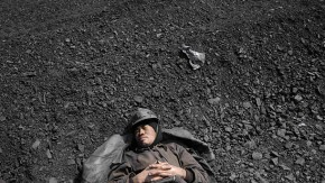 Một công nhân lò than kiệt sức ngủ thiếp ngay tại một lò than tại Trung Quốc.