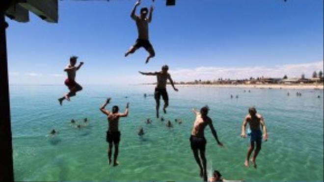 Trong khi ở Châu Âu đang trong mùa tuyết lạnh, nước Úc lại hừng hực đón Giáng sinh với nhiệt độ 42 độ C. Người dân và khách du lịch nhảy xuống biển để bơi cho mát tại . Henley, phía nam Adelaide, Úc.