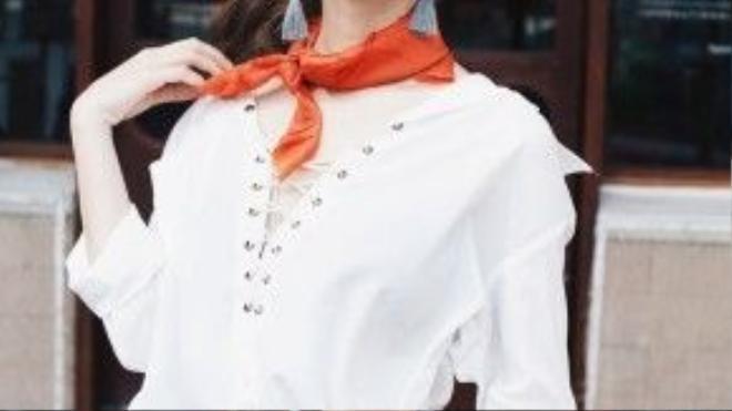 Với kiểu áo khoe nét nữ tính của cổ và vai, khăn lụa vuông với màu cam rực rỡ thắt hờ và hoa tai tua rua là cách hoàn hảo để làm điểm nhấn và che đi những khoảng trống.
