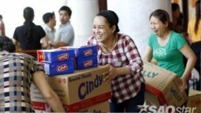 Trong khi đó, các tình nguyện viên bên ngoài sảnh hội trường tích cực hỗ trợ việc chia và phát những phần quà khác do các nhà hảo tâm tặng thêm cho chương trình.