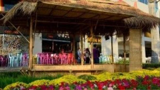 Tiểu cảnh những ngôi nhà tranh mái rơm đơn sơ nằm bên đường làng quanh co, xung quanh phủ đầy hoa các màu sắc.