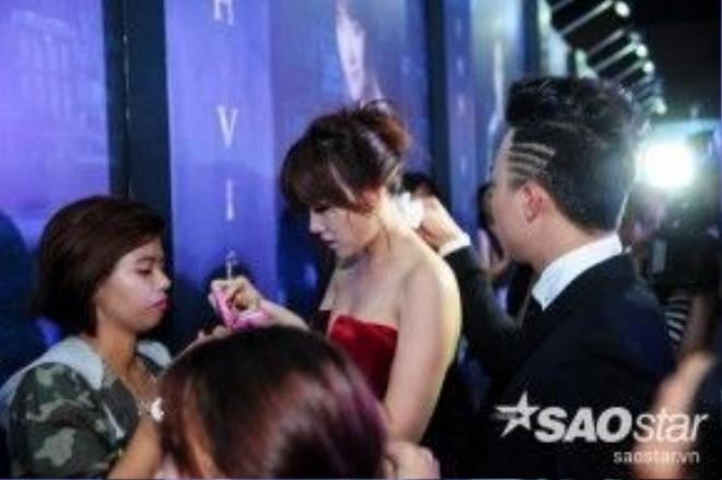Khi đang tham dự buổi lễ, Hari Won muốn trang điểm lại. Trấn Thành đứng sau ân cần lau mồ hôi cho người yêu.