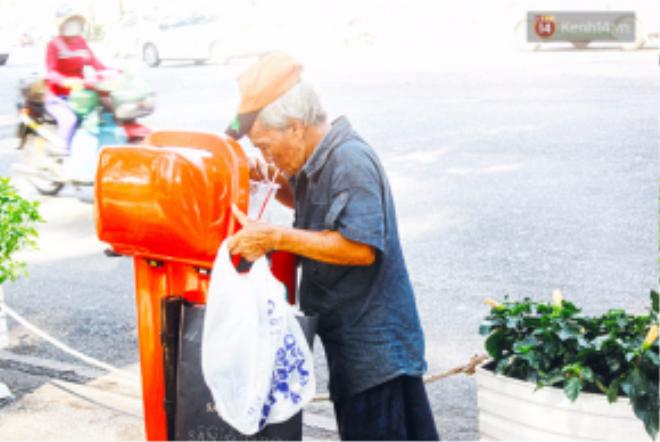 Người đàn ông cắm cúi tận hưởng ly cà phê vừa tìm được trong thùng rác.