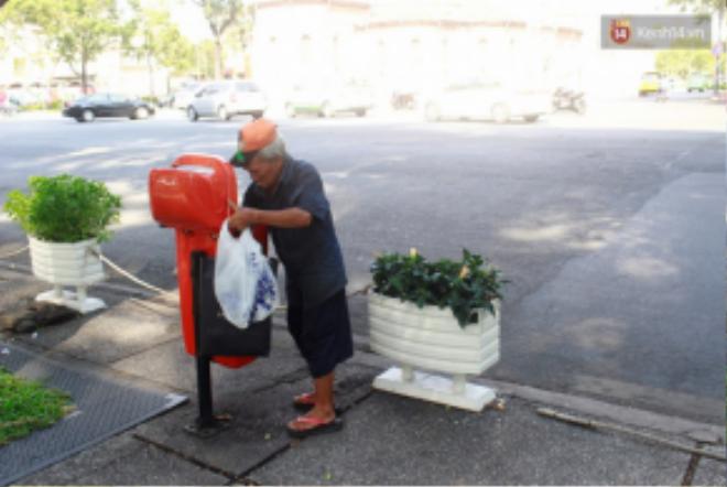 Ông tìm kiếm chai nước, vỏ lon từ trong thùng rác.