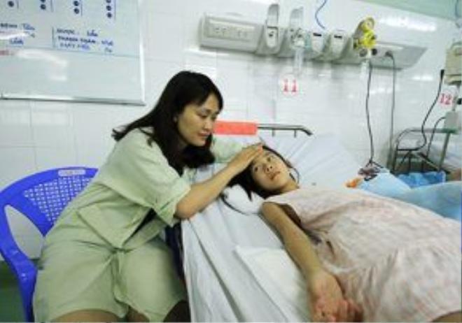 Chị Thúy chăm sóc con gái Bảo Hân tại bệnh viện. Trong đêm 4/6, Bệnh viện Phụ sản - Nhi Đà Nẵng đã tiếp nhận 16 bệnh nhi vụ chìm tàu. Ảnh: Nguyễn Đông.