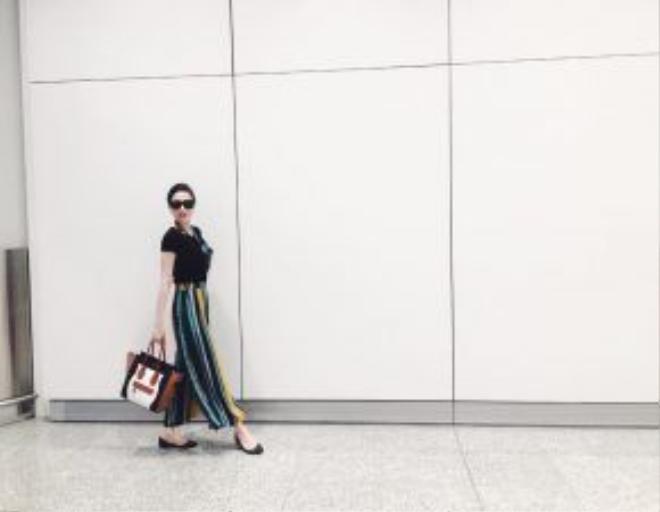 Bảo Thy lạ lẫm với xu hướng ngẫu hứng màu sắc đang làm mưa làm gió trong giới thời trang. Việc kết hợp mẫu quần kẻ sọc ống rộng cùng với áo thun đen đơn giản cũng chính là một trong những lựa chọn thông mình, vừa tiết chế được họa tiết cũng như tạo ra sự nổi bật nhất định cho người mặc.