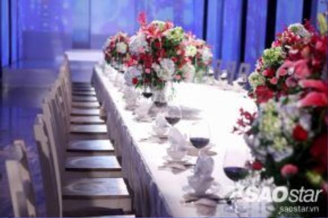 Bàn tiệc đươc thiết kế cầu kì sang trọng với những lẵng hoa lớn, rượu vang và nến nhưng có diện tích khá khiêm tốn trước rất nhiều khách mời.