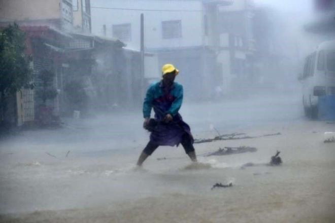Một người dân ở huyện Bình Đông dọn dẹp đá và chướng ngại vật trên một con đường trong mưa bão. Theo CNN, đã có 2 người bị thương do bão Meranti.