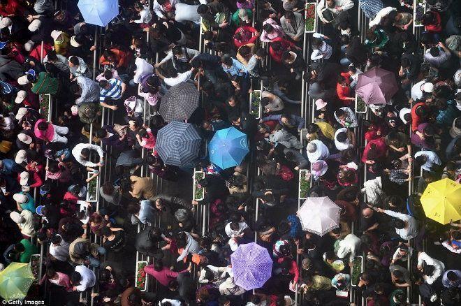 Cảnh tượng đông đúc trong một ngày mưa gần tòa nhà China Pavilion, Thượng Hải. Ảnh: Getty.