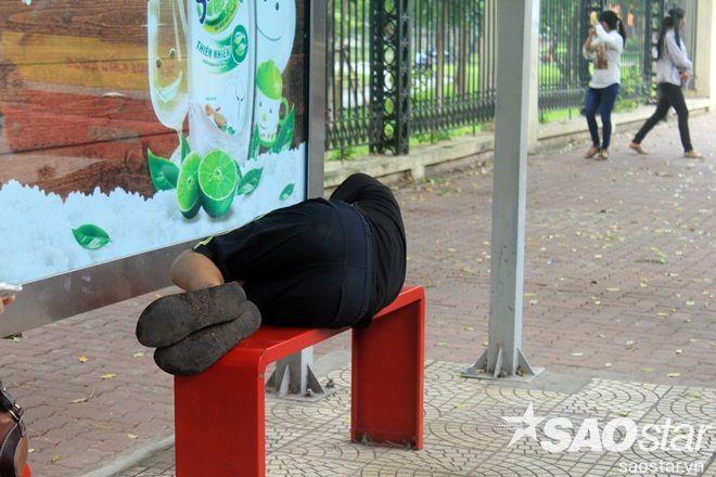 Người đàn ông vô gia cư nằm ngủ trên ghế chờ xe buýt co ro trong cái lạnh đầu mùa.