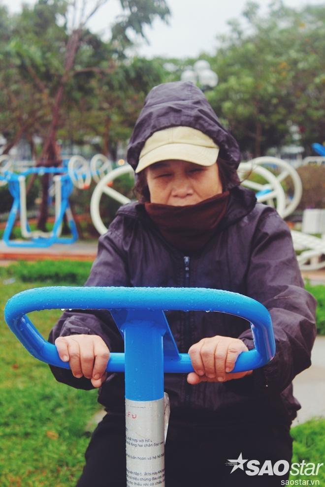Một cụ già tập thể dục nhưng phải mặc áo khoác kín mít để giữ ấm.