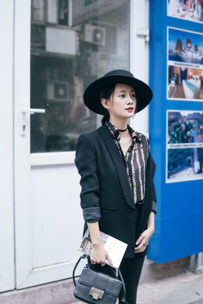 Xu hướng mặc áo lệch vai cũng được nữ BTV áp dụng vào phong cách của chính mình. Cô nàng lựa chọn cho mình mẫu áo voan kẻ sọc hòa phối cùng suit đen và điểm nhấn trên toàn set đồ lại đến từ chiếc nón Fedora cùng vòng choker cá tính.