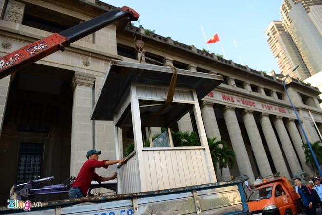 Lực lượng chức năng quận 1 tháo dỡ chốt bảo vệ Ngân hàng Nhà nước Việt Nam. Ảnh: Tùng Tin.