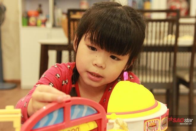 Vẻ tập trung của bé Miu khi lắp ghép ngôi nhà đồ chơi.