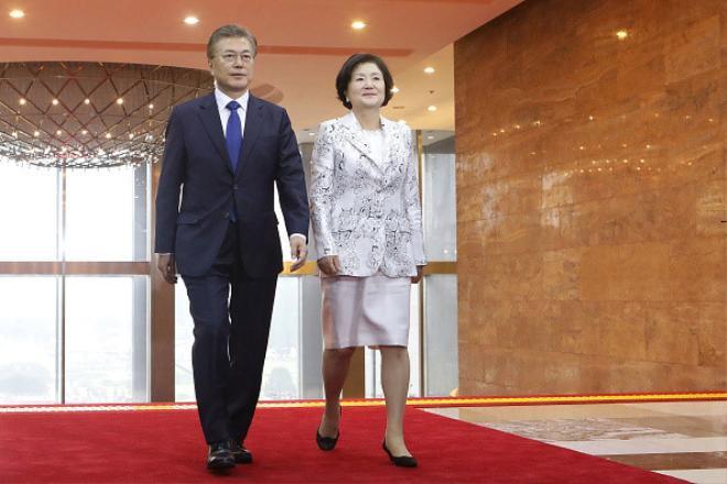 """Ông Moon Jae In và phu nhân Kim Jung Sook bước vào tòa nhà Quốc hội để dự lễ nhậm chức tổng thống tại Seoul ngày 10/5. Trong chiến dịch tranh cử tổng thống ngắn ngủi nhưng căng thẳng kéo dài 60 ngày, bà Kim đã nhận được sự tín nhiệm rộng rãi khi góp phần thúc đẩy sự ủng hộ cho chồng bà ở khu vực tỉnh Jeolla, phía tây nam Hàn Quốc.Tại đây, bà được đặt biệt danh """"người phụ nữ vui tính"""" vì tính cách dễ mến và dễ trò chuyện của bà. Trợ lý của ông Moon nói rằng tính cách của bà Kim đã giúp làm dịu bớt cá tính mạnh mẽ của tổng thống.Ảnh: Getty."""