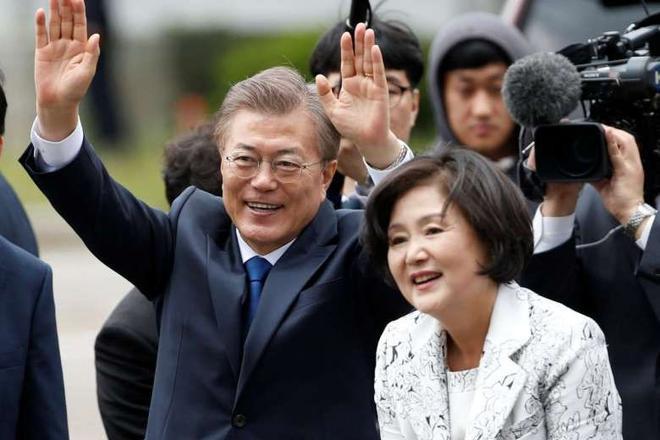 """Tổng thống Moon Jae In và phu nhân Kim vẫy tay chào mọi người khi tới phủ tổng thống ở Seoul, Hàn Quốc, ngày 10/5. Khi được hỏi về vai trò của bà sau khi trở thành đệ nhất phu nhân của Hàn Quốc, người phụ nữ 62 tuổi này nói: """"Tôi muốn sẽ vẫn là chính mình, giống như tôi vẫn luôn như vậy. Một đệ nhất phu nhân có thể giao tiếp với mọi người, giống như mọi người, tôi gọi đó là phong cách Kim Jung Sook"""".Ảnh: Reuters."""