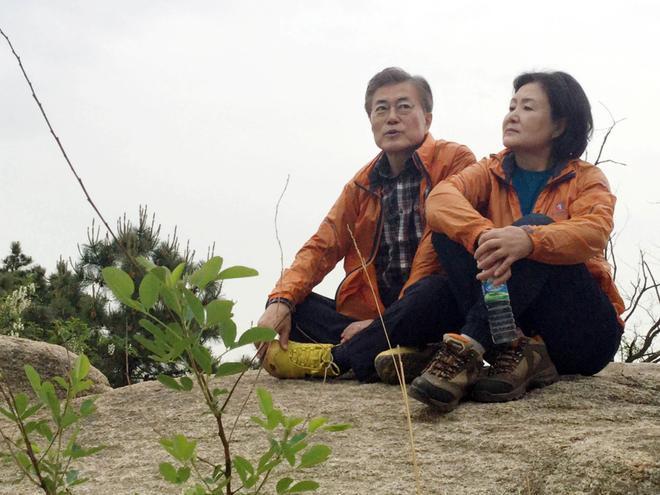 """Ông Moon và bà Kim ngồi nghỉ trên dãy núi phía sau nhà riêng của họ tại Seoul, Hàn Quốc. Vợ chồng họ có 2 người con. """"Chồng tôi từng nói sau khi trở thành tổng thống, ông ấy muốn có thể đi quaQuảng trường Gwanghwamun trên đường về nhà sau giờ làm việc để uống một chút rượu soju với mọi người. Giống như ông ấy, tôi muốn đi mua sắm ở các cửa hàng tạp hóa trong chợ Namdaemun"""", bà Kim nói vớiKorea Herald.Ảnh: Reuters."""